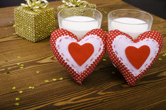 Two hearts and two golden gift and two glasses of milk. Stock Photography