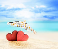 Two hearts under umbrella on a sandy beach. Two red hearts under umbrella on a sandy beach Royalty Free Stock Photos