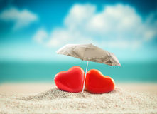 Two hearts under umbrella on the summer beach. Valentines day Royalty Free Stock Image