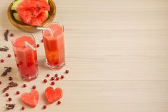 Two hearts, watermelon juice in two glass glasses with a straw on a light wooden background, a delicious cocktail, a Royalty Free Stock Images