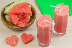 Two hearts, Watermelon juice in two glass glasses with a straw on a light wooden background, a delicious cocktail, a Royalty Free Stock Image