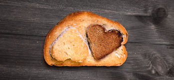 Two hearts which are cut out from white and rye bread are insert Stock Photos