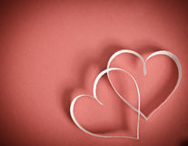 Two hearts of white paper on a red background Stock Photos