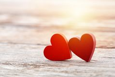 Two hearts on wooden background Stock Photos