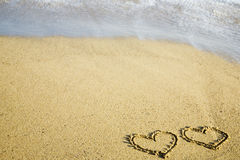 Two hearts written on sand Royalty Free Stock Photos