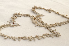 Two hearts written in sand on a beach Stock Images