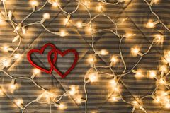 Two hearts with yellow lights, cozy couple concept, Valentine`s Day. Flat lay royalty free stock photo
