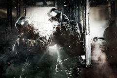 Two heavily armed masked paintball soldier on post apocalyptic background. Ad concept. stock photos