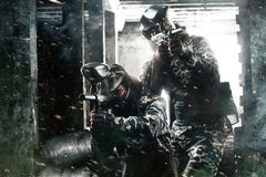 Two heavily armed masked paintball soldier on post apocalyptic background. Ad concept. royalty free stock photo