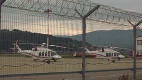 Helicopter behind the fence. Two helicopters standing on pad or platform against background with sunset, mountain covered with forests and metal fence or barbed stock video