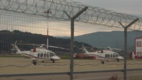 Helicopter behind the fence. Two helicopters standing on pad or platform against background with sunset, mountain covered with forests and metal fence or barbed stock video footage