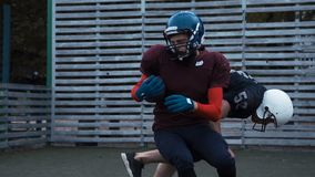 Two helmeted football players. Slow motion of two helmeted football players in two different uniforms pushing past each other with fence in background stock video