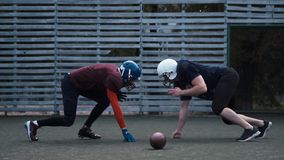 Two helmeted football players. Slow motion of two helmeted football players in two different uniforms pushing past each other with fence in background stock footage