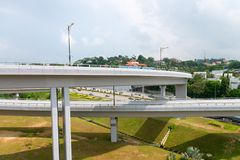 Two high overpasses on a modern town. Two high overpasses on modern wide road with buildings in green trees on background Royalty Free Stock Photo