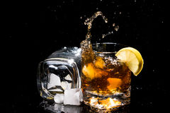 Two high quality glasses of whiskey with falling ice and lemon with splashes. Royalty Free Stock Photography