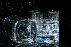 Two high quality glasses of whiskey, one lies on side and other with ice cubes and water splashes. Stock Images