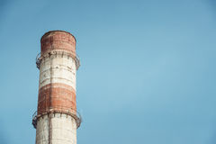 High red-white industrial factory pipes on the blue sky Royalty Free Stock Images