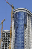 Two high-rise buildings under construction and cranes. Close-up Royalty Free Stock Photo