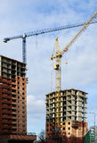 Two high-rise houses and two cranes. Two high-rise building under construction on the background of the sky and construction cranes Royalty Free Stock Photography