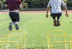 Two athletes jumping over yellow hurdles Royalty Free Stock Photos