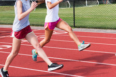 Two high school girls do running drills on a red track Royalty Free Stock Images