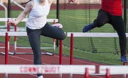 Two high school girls racing the hurdles outside. Two high school girls are racing each other in the 100 meter high hurdles during a track and field competition stock photos