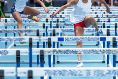 Two high school girls racing the hurdles at a track meet Royalty Free Stock Image