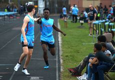 Two high school students pass the baton in the 3000 meter relay race. stock images