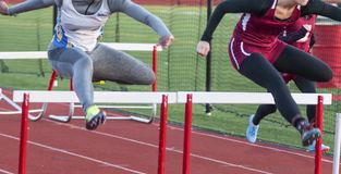 Two high school teenage girls racing in the hurdles. Two high school teenage girls are neck and neck during a hurdle race competition on an outdoor track royalty free stock images