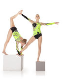 Two high skill acrobats stand on cube. Two high skill acrobats exercise program on cube isolated Royalty Free Stock Photography