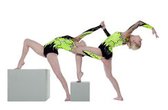 Two high skill woman as gymnast dance on cube. Two high skill acrobats exercise program on cube isolated Royalty Free Stock Photography