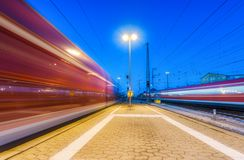 Two high speed trains in motion on the railway station at night Royalty Free Stock Image