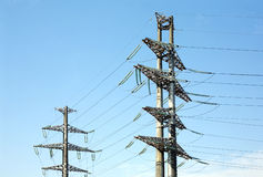 Two high-voltage power line metal props over blue sky Royalty Free Stock Photography