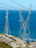 Two High voltage towers. Next to the sea Royalty Free Stock Photos