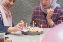 Two hijab bestfriend preparing birthday surprise party sitting together at the concrete table. With gift and pancake stock images