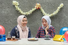 Two hijab bestfriend preparing birthday surprise party sitting together at the concrete table. With gift and pancake stock photos