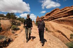 Two hikers. On a sandstone slab Stock Photos