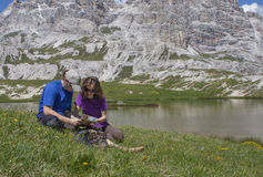 Two hikers by the alpine lake. Two young hikers by the alpine lake having rest and studying the map Royalty Free Stock Photography