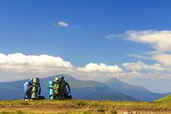 Two hikers backpacks on a grass with mountain peaks in view. Car Royalty Free Stock Photography