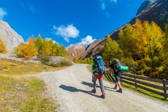 Two hikers with backpacks on a road to Grossglockner in autumn, Tyrol, Austria stock image