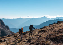 Two Hikers with Backpacks walking on grassy heel in Mountains Royalty Free Stock Image