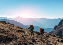 Two Hikers with Backpacks walking on grassy heel in Mountains. Two Hikers with Backpacks and walking Sticks walking on grassy Trail towards rising Sun. Layered Stock Photography