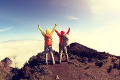 Two hikers cheering to sunrise on mountain peak Stock Images