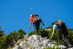 Two hikers climbing towards the moon Stock Image