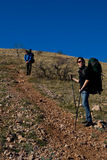 Two hikers climbing up the mountain. Two hikers with backpacks climbing up rocky mountain Stock Photos