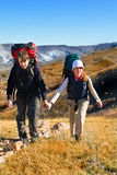 Two hikers climbing up the mountain. Couple of hikers with backpacks climbing up rocky mountain Stock Photos