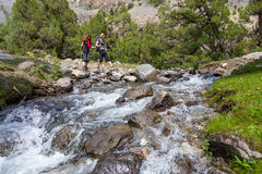 Two hikers crossing fast flowing river Stock Photos