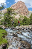 Two hikers crossing fast flowing river Royalty Free Stock Photo