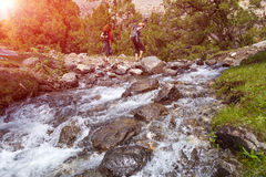 Two hikers crossing fast flowing river Royalty Free Stock Images