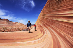 Two Hikers Entering The Wave. Petrified sandstone formations at The Wave in the Coyote Buttes section of the Paria Canyon-Vermilion Cliffs Wilderness in northern Stock Photo
